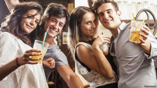 Две молодые пары выпивают в баре