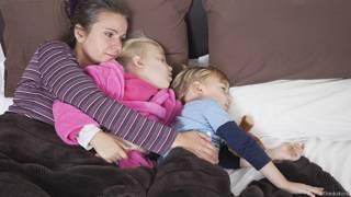 Мать-одиночка с двумя детьми в постели