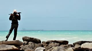 Сомалийский пират, на горизонте захваченный южнокорейский танкер