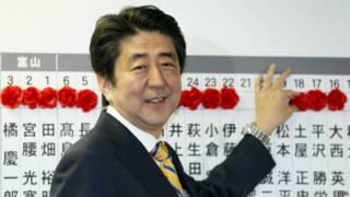 安倍晋三在给众议院选举当选者贴上红花标记