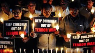 """Мужчины со свечами и плакатом """"Избавьте детей от террора войны"""""""