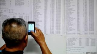 Homem olha lista de passageiros de voo desaparecido (foto: Getty)