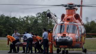 印尼龐卡蘭邦軍事基地數名國家搜索與拯救局人員將一具QZ8501遇難者遺體卸下直升機(31/12/2014)