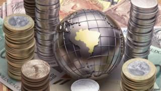 Monedas de reales brasileños junto a un globo terráqueo con el mapa de Brasil.