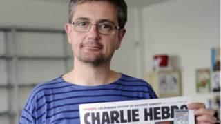 ستيفان شاربونييه يحمل عددا من مجلة شارلي إبدو