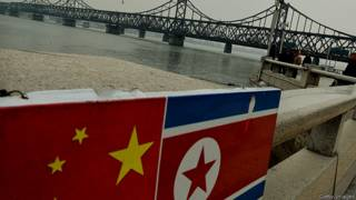 Флаги Китая и Северной Кореи на границе между двумя странами