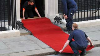 Workers roll out a red carpet
