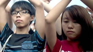 黃之鋒(左)與錢詩文(右)在金紫荊廣場外舉起抗議手勢(1/10/2014)