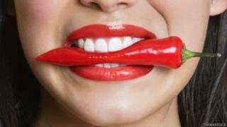 Mujer con un chile en la boca