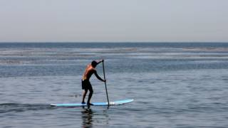 A man paddle surfing in California