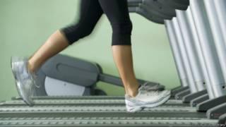 Женщина на бегущей дорожке в гимнастическом зале
