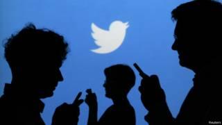 Personas usando su celular con pájaro de Twitter en el fondo.