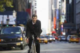 Мужчина в костюме на велосипеде