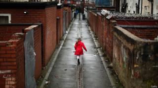 Девочка играет в переулке Манчестера