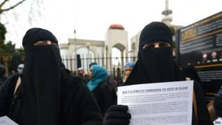Женщины в никабах раздают листовки с призывом не участвовать в выборах в Лондоне