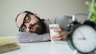 Hombre durmiendo sobre escritorio