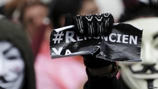 Un manifestante en Guatemala muestra el hashtag #RenunciaYa