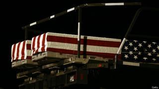 Погибших американских солдат перевозят на родину в гробах, покрытых национальными флагами