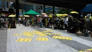 反對政改方案的「全民拒絕假普選運動」在立法會外示威區地上用宣傳張貼,擺出「否決」的字樣
