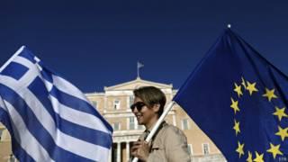 Manifestante pró-zona do euro diante do Parlamento grego nesta segunda-feira (EPA)