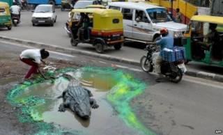 Nghệ sĩ Ấn Độ đặt cá sấu giả vào ổ gà khủng bên đường