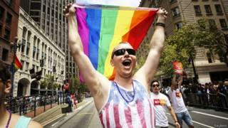 Мужчина с радужным флагом на параде в Сан-Франциско