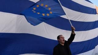 Мужчина с флагом Евросоюза на фоне греческого флага