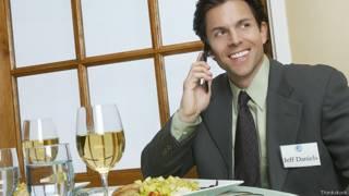 Бизнесмен в ресторане говорит по телефону