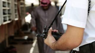 شرطي سعودي يحمل بندقية