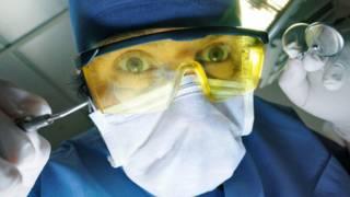 Un dentista que se aproxima con sus instrumentos
