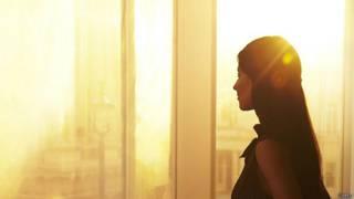 Женщина ранним утром на фоне окна