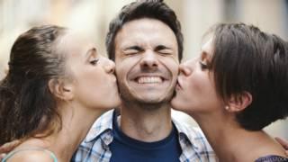 Unas chicas besan a un joven