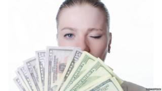 Una mujer detrás de un manojo de billetes