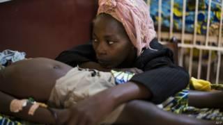 Mãe acompanha criança com malária (Foto: AFP)
