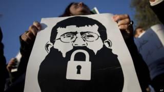 Женщина держит плакат с изображением Хадера Аднана с замком вместо рта