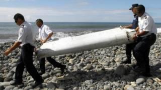Люди несут обломок, выброшенный на берег острова Реюньон