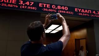 Мужчина фотографирует биржевые индексы