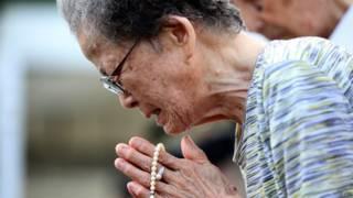 Женщина плачет в Парке мира в Нагасаки