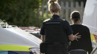 Viên chức di trú bắt một di dân bất hợp pháp trong một cuộc truy quét ở during raid in Slough, Berkshire, Anh Quốc