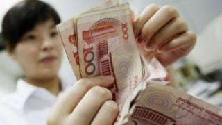 Una mujer cuenta billetes de yuan, la moneda china que se ha devaluado por tercer día consecutivo.
