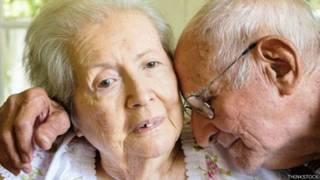 Señora con demencia, abrazada por su esposo