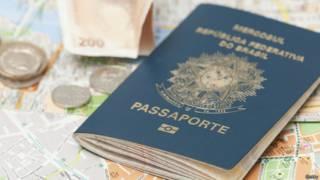 Un pasaporte brasileño descansa junto a monedas y un mapa.