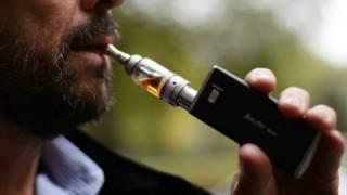 一名吸烟者正在吸电子烟。对于电子烟,目前各种机构有不同看法。