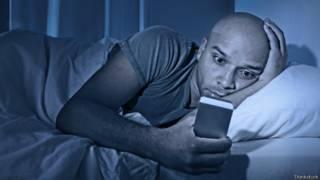 Hombre viendo celular en la cama