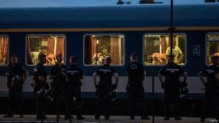 قطار اللاجئين يصطف أمامه رجال الشرطة