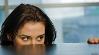 Девушка прячется за рабочим столом