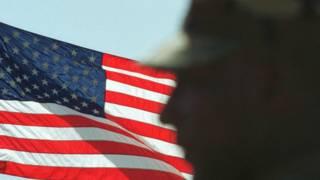 La silueta de un soldado frente a una bandera estadounidense