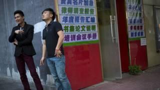 两名男性烟民在北京一栋大厦外吸烟。