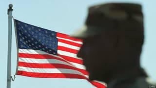 Американский солдат на фоне флага в ДМЗ