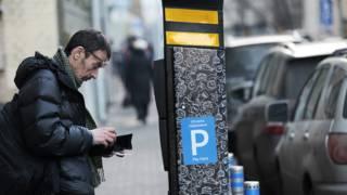 Мужчина платит за парковку